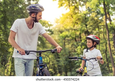 Handsome young dad and his cute little son are looking at each other and smiling while riding bikes in park