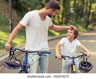 Handsome young dad and his cute little son are looking at each other and smiling while riding bikes in park. Father is patting his son