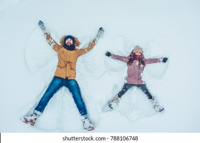 Handsome young dad and his little cute daughter are having fun outdoor in winter. Enjoying spending time together while making snow angels. Family concept.