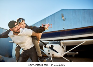 handsome young dad holding on his back little son in aviator glasses and large pilot jacket, holding handmade toy plane, playing outside aircraft shed, smiling and feeling happy.