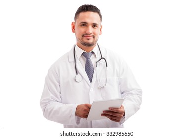 Handsome young doctor with a lab coat and stethoscope using a tablet computer to check a patient's history