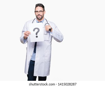 Handsome young doctor man holding paper with question mark over isolated background with surprise face pointing finger to himself