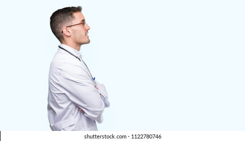 Handsome young doctor man looking to side, relax profile pose with natural face with confident smile.