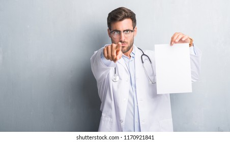 Handsome young doctor man over grey grunge wall holding blank sheet contract pointing with finger to the camera and to you, hand sign, positive and confident gesture from the front