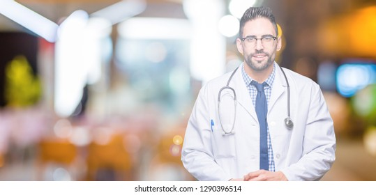 Handsome young doctor man over isolated background Hands together and fingers crossed smiling relaxed and cheerful. Success and optimistic