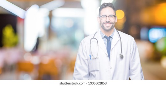 Handsome young doctor man over isolated background with a happy and cool smile on face. Lucky person.