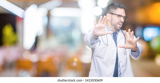 Handsome young doctor man over isolated background afraid and terrified with fear expression stop gesture with hands, shouting in shock. Panic concept.