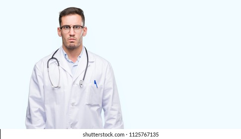 Handsome young doctor man skeptic and nervous, frowning upset because of problem. Negative person.