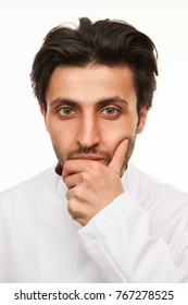 Handsome young doctor in uniform thinking about treatment, looking at camera isolated on white, close-up portrait