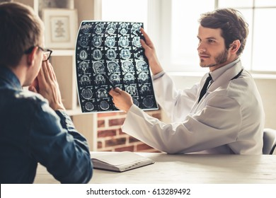 Handsome young doctor in white coat is showing x-ray image to his patient while working in office