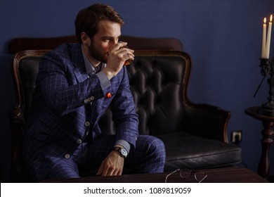 Handsome young elegant man in a classic suit drinking beverage sitting at chesterfield settee in restaurant