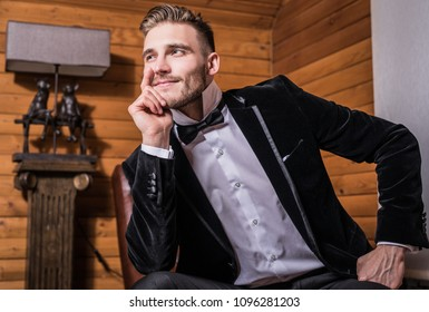 Handsome young elegant man in costume & bow tie pose against house interior.