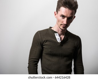 Handsome young elegant man in dark green t-shirt pose against gray studio background.