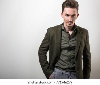 Handsome young elegant man in dark green jacket pose against gray studio background.