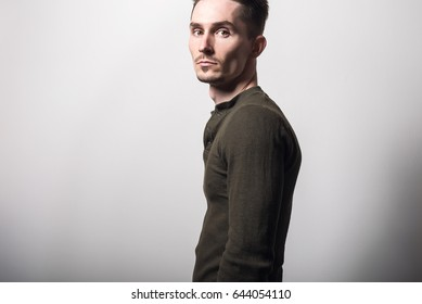 Handsome young elegant man in green t-shirt pose against gray studio background.