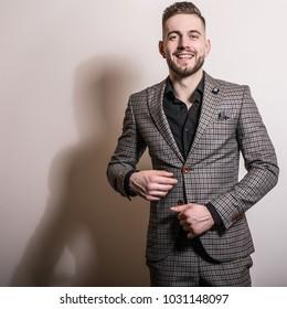 Handsome young elegant man in grey jacket pose against studio background.