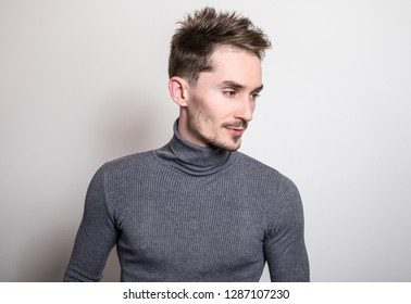 Handsome young elegant man in grey golf.