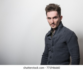 Handsome young elegant man in grey switer pose against studio background.