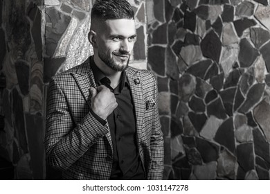 Handsome young elegant man pose against house interior. Black-white portrait.
