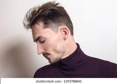 Handsome young elegant man in violet golf.