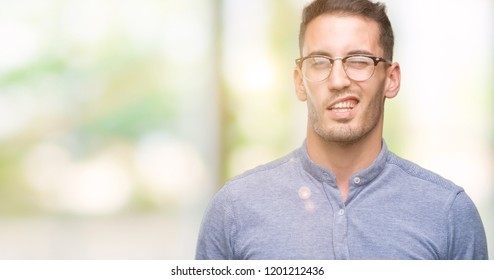 Handsome young elegant man wearing glasses winking looking at the camera with sexy expression, cheerful and happy face.