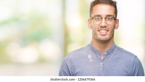 Handsome young elegant man wearing glasses with a happy and cool smile on face. Lucky person.