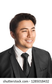 Handsome young entrepreneur with a smile standing against a white background wearing a grey suit, tie and vest.