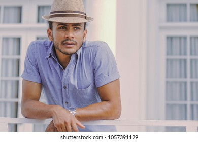 Handsome young ethnic man standing at the handrail of the balcony and looking away outdoors.