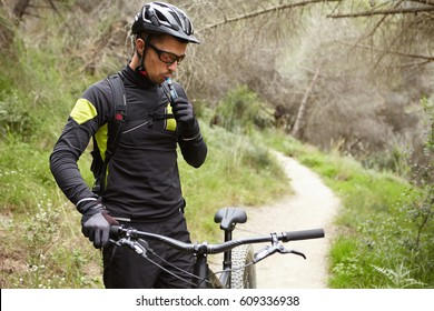 Handsome young European mountain biker in sports wear and protective gear standing on trail in forest with his electric motor-powered bicycle, having small break, drinking water out of plastic tube