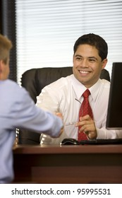 Handsome young executive male shaking hands in office.
