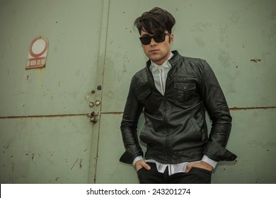 Handsome young fashion man leaning on a green metal door with his hands in pockets.