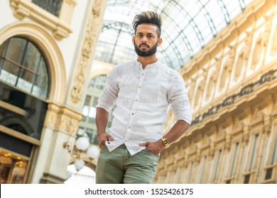 Handsome young fashion model posing on city streets. Outdoor fashion portrait, stylish man in elegant shart. Lifestyle concept.