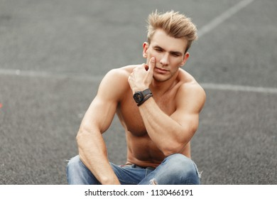 Handsome young fashionable man with a hairstyle with a naked torso sitting on the street