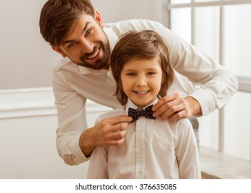 Handsome young father adjusting his cute little son's bow tie. Both white classical shirts looking in camera and smiling
