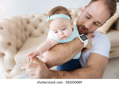 Handsome young father amusing his toddler girl at home