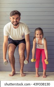 Handsome young father and his cute little daughter are looking at camera and smiling while working out with dumbbells at home