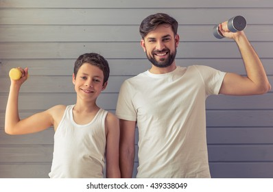 Handsome young father and his teenage son are looking at camera and smiling while working out with dumbbells