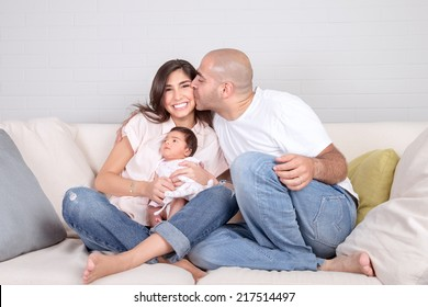 Handsome young father kissing beautiful smiling mother with cute newborn baby on hands, having fun together at home, loving family concept