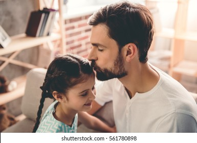 Handsome young father is kissing his cute little girl in forehead. Both are sitting on couch at home