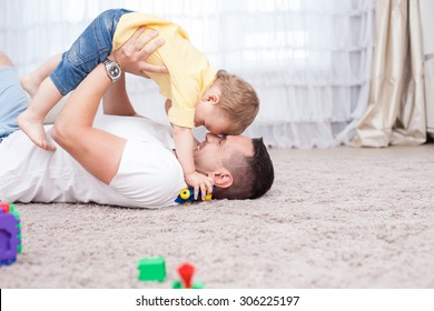 Handsome young father is playing with his sun. He is lying on flooring and holding the child under him with joy. They are smiling. Copy space in right side