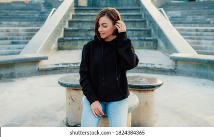 Handsome young female wearing black blank hoodie with space for your logo or design. Mockup for print