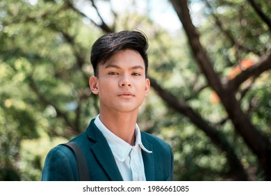 A handsome and young Filipino college student in smart casual wear. Serious look. At the park or campus grounds.