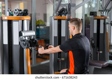 Handsome young fit man training on row machine in gym room in fitness center