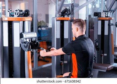 Handsome young fit man training on modern row machine in gym room in fitness center