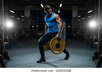 Handsome young fit muscular caucasian man of model appearance workout training in the gym gaining weight pumping up muscles and poses fitness and bodybuilding sport concept