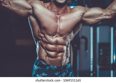 Handsome young fit muscular caucasian man of model appearance workout training in the gym gaining weight pumping up muscle and poses fitness and bodybuilding sport nutrition concept