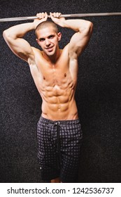 Handsome young fitness man, shirtless, posing in gym on dark background, smiling. Studio lighting, mild retouch.