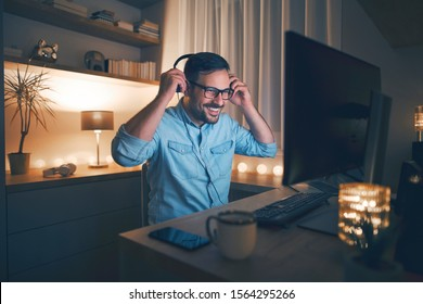 Handsome young freelancer working remotely at night. He is putting on headphones.