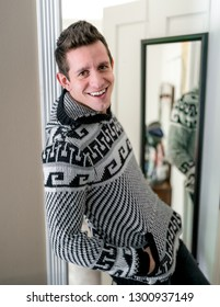 A handsome young gentleman wearing a patterned winter sweater, leaning in the doorway of a room in front of a mirror smiling at the camera with excitement and content.