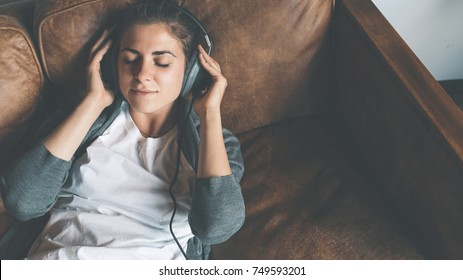Handsome young girl listening to music from headphones with pleasure at coworking office, lying on sofa and resting.